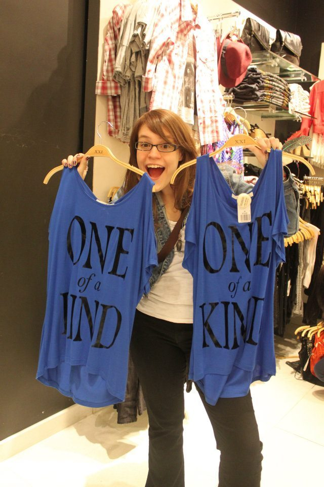 "Photo of Shannon holding two identical shirts saying ""One of a kind"""